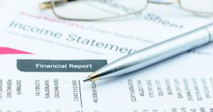 Pen on a financial report - Financial investment analysis concept